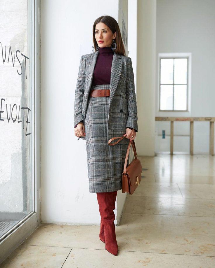 """На девушке тёмно-бордовая водолазка с воротом, серый костюм с принтом гленчек: прямая юбка длины миди с кожаным коричневым ремнем и пиджак прямого кроя, красные замшевые ботфорты """"гармошкой"""", кожаная коричневая сумка."""