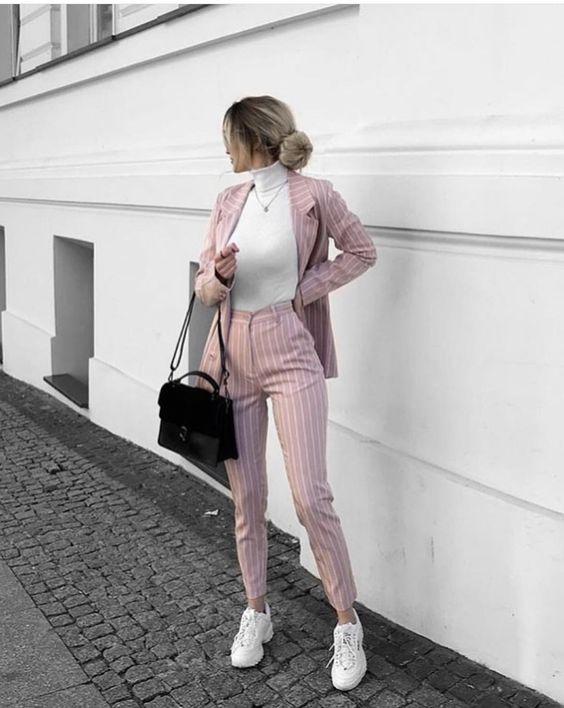 Белая, плотно облегающая, водолазка с воротом в сочетании со светло-розовым костюмом в белую вертикальную полоску: классический удлиненный пиджак и облегающие брюки с высокой талией, белые кроссовки, черная сумка-мессенджер.