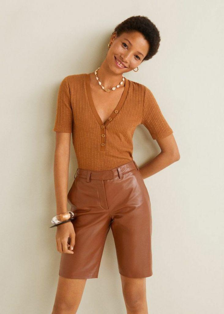 На девушке песочная водолазка в рубчик с короткими рукавами и глубоким v-образным декольте с пуговицами, кожаные коричневые шорты-бермуды, серьги и ожерелье.