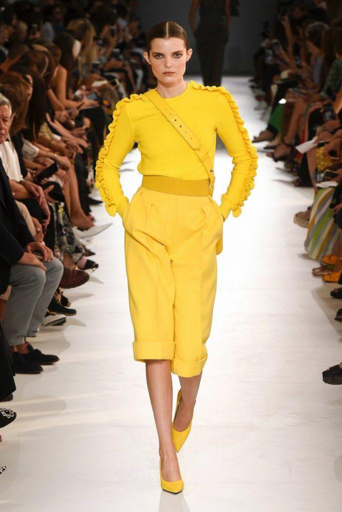 На модели желтая водолазка без ворота, декорированная рюшами на рукавах, желтые свободные шорты-бермуды по колено и с резиновым поясом, желтые лодочки с заостренным носом на каблуке.