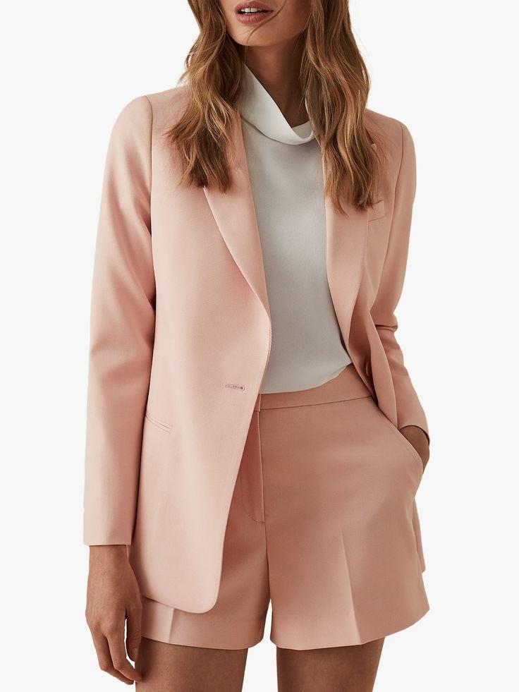 Белая водолазка со свободным воротом в сочетании с нежно-розовым пиджаком прямого кроя и короткими свободными шортами с завышенной талией.