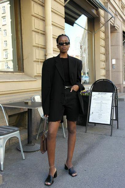 На девушке черная водолазка без ворота, джинсовые черные велосипедки с кожаным ремнем, черный пиджак оверсайз, квадратные очки и кожаные черные босоножки с квадратным носом и открытой пяткой.