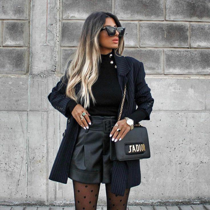 Черная облегающая водолазка с декорированным воротом в виде металлических пуговиц в сочетании с свободными кожаными черными шортами с присборенной высокой талией чёрным пиджаком в белую полоску. Образ дополнен аксессуарами : поясной черной сумкой, кольцами, часами и чёрными очками.