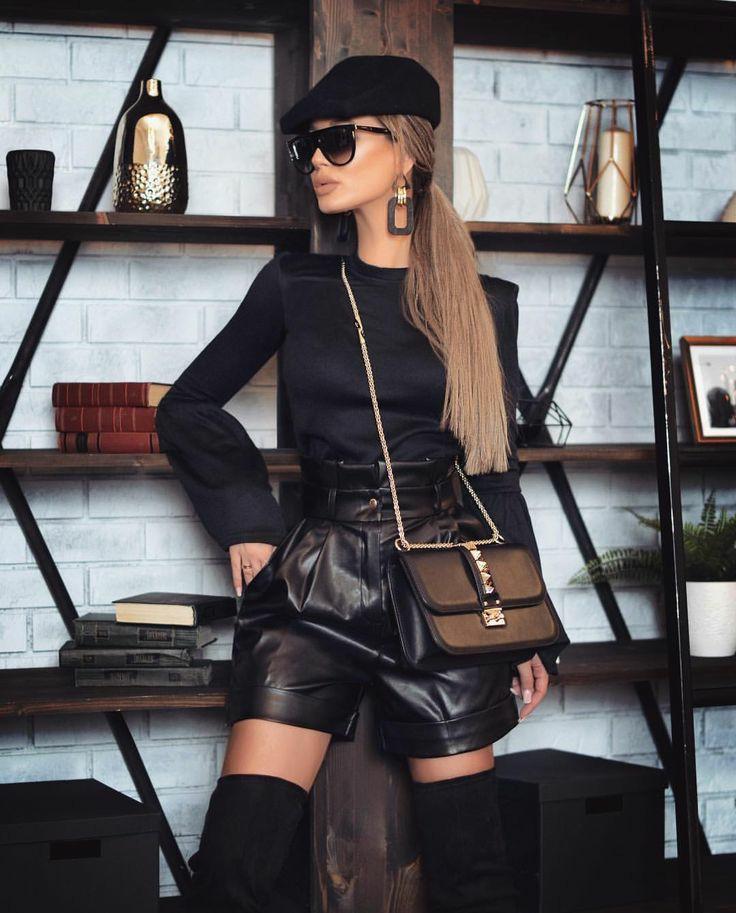 На девушке черная облегающая водолазка без ворота и с пышными рукавами, свободные кожаные шорты с завышенной талией, замшевые ботфорты выше колена, черная поясная квадратная сумка, черная кепи, объемные серьги и очки.
