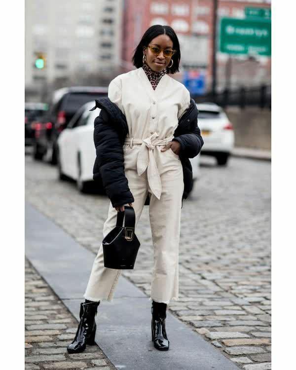 На девушке белый хлопковый комбинезон с v-образным вырезом, поясом и пуговицами, леопардовая водолазка с воротом, лаковые ботильоны на толстом высоком каблуке, черная дутая куртка. Образ дополнен черной кожаной сумкой необычной формы, светло-коричневыми очками и круглыми серьгами.