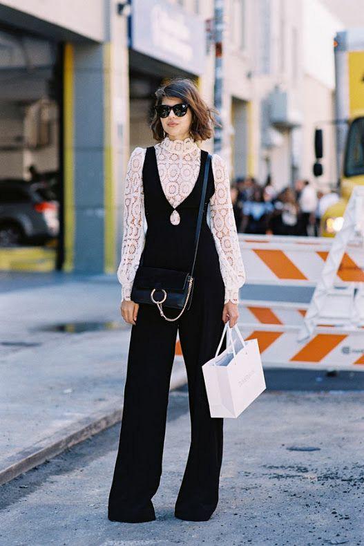 На девушке белая водолазка с ажурным узором, пышными рукавами и воротом, черный облегающий костюм с длинными брюками, поясная сумка с золотой цепочкой, черные очки.