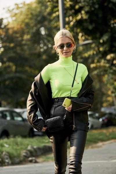 На девушке неоновая облегающая водолазка с горлом, черная косуха оверсайз, черные кожаные брюки с высокой талией. Образ подчеркивают аксессуары: поясная квадратная сумочка, очки, длинная тонкая цепочка.