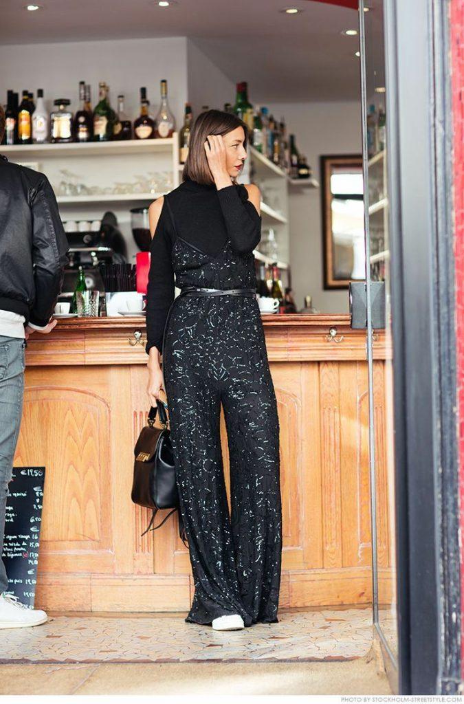 На девушке черная водолазка с вырезами на плечах, черный комбинезон с пышными брюками , декорированными бисером и кожаным тонким ремнем, белые кеды, черная кожаная сумка.
