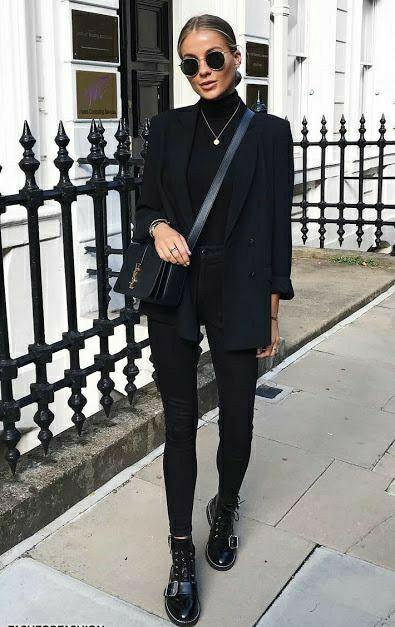 На девушки черный total look: водолазка с высоким горлом, джинсы скинни с завышенной талией, удлиненный пиджак прямого кроя, ботинки на шнуровке и с ремешками, поясная квадратная сумка, круглые очки и тонкая цепочка.