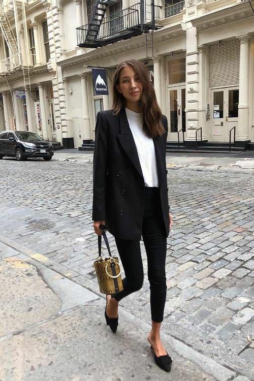 Белая водолазка с невысоким воротам в сочетании с черным пиджаком оверсайз, черными джинсами скинни, туфлями с заостренным носом и без пятки, коричневой сумкой-футляр.