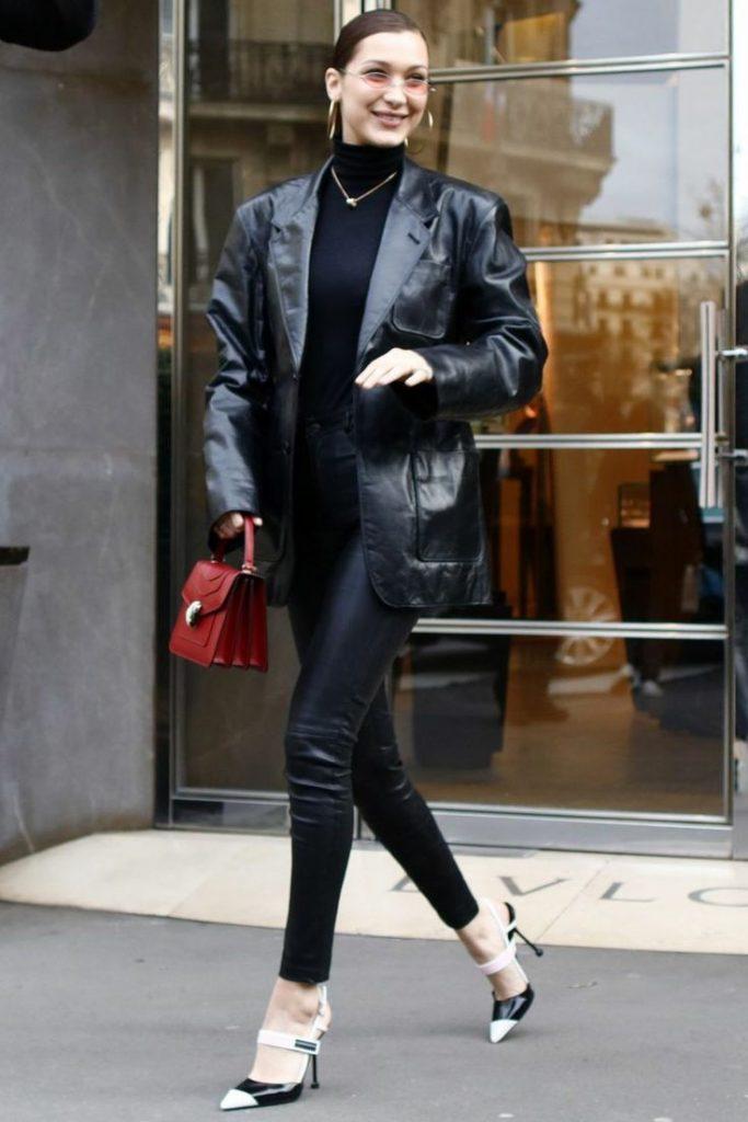 На девушке черная водолазка с воротом, кожаные облегающие брюки, кожаный черный пиджак оверсайз, черно-белые лодочки с заостренным носом и на тонком каблуке, красная маленькая квадратная сумка, тонкая цепочка, светло розовые круглые очки и серьги.