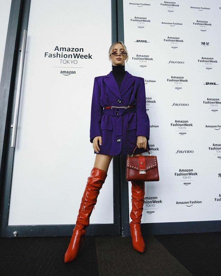 """На девушке черная облегающая водолазка с высоким воротом, яркий фиолетовый пиджак оверсайз с широким ремнем, красные кожаные ботфорты """"гармошкой"""" выше колена, красная квадратная сумка и узкие круглые очки."""