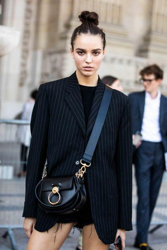 Черная водолазка без ворота в сочетании с черным пиджаком прямого кроя в белую горизонтальную полоску и кожаной поясной круглой сумкой.