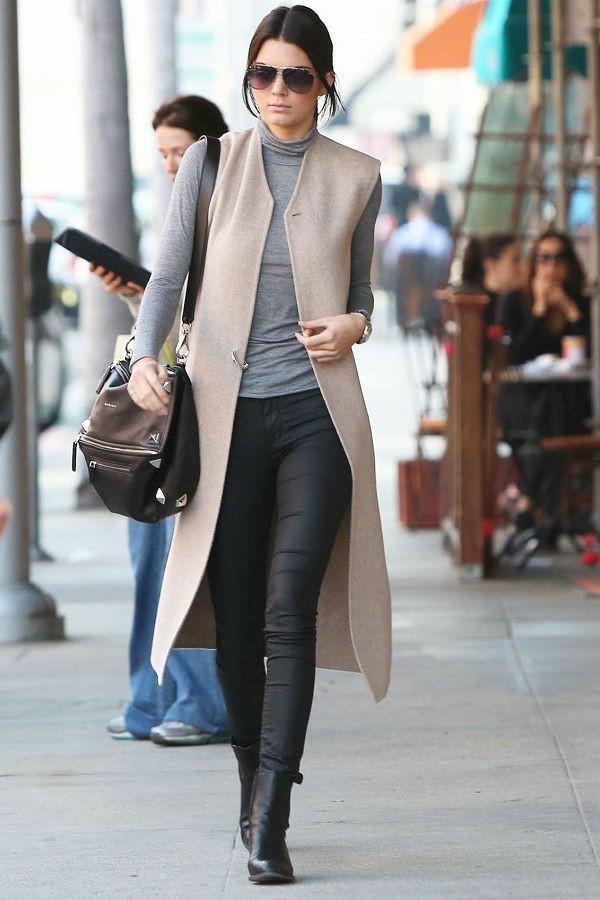 На девушке тонкая серая водолазка с длинным воротом, кожаные облегающие брюки, бежевый жилет длины миди, кожаные черные ботинки, очки и сумка.