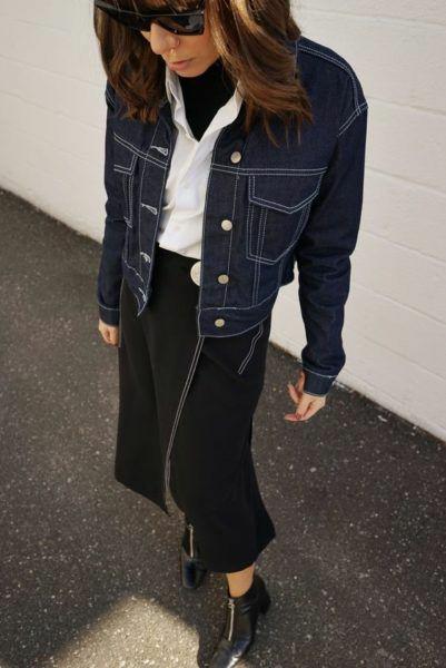 На девушке черная водолазка с высоким воротом, белая рубашка, свободная черная юбка длины миди на запах, черные кожаные ботинки с квадратным носом и толстым маленьким каблуком, змейкой, темно-синяя джинсовая куртка, черные квадратные очки.