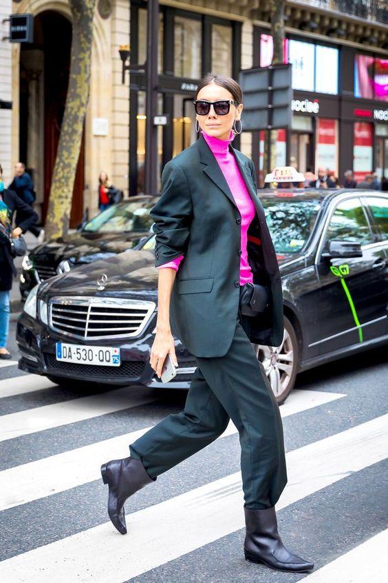 """Яркая розовая водолазка с рукавом в три четверти в сочетании с черным костюмом в мужском стиле: пиджак оверсайз с укороченным рукавом """"гармошка"""", свободные брюки, кожаными ботинками с широким голенищем и заостренным носом, поясной сумкой-клатчем, квадратными очками."""