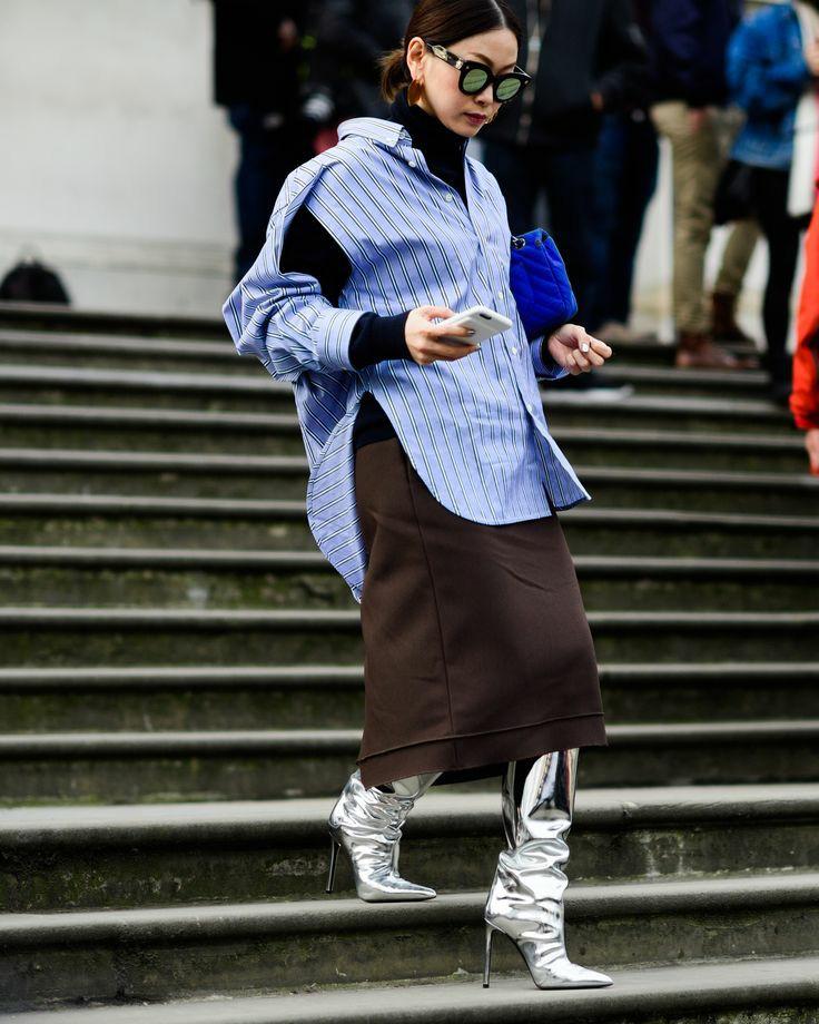 На девушке черная плотная водолазка с воротом, голубая рубашка оверсайз в горизонтальную полоску с разрезами и вырезами на рукавах, коричневая прямая юбка ниже колена, металлические ботфорты на шпильке и с заостренным носом, синий клатч и солнцезащитные очки.