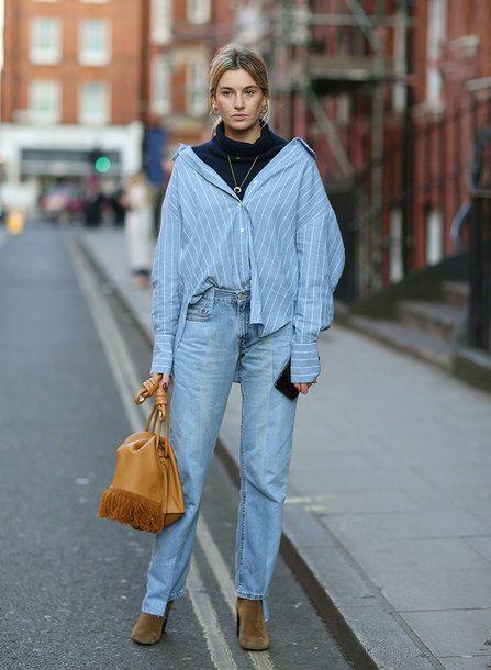 Черная водолазка с объемным воротом в сочетании с голубой рубашкой мужского кроя в белую горизонтальную полоску, голубыми прямыми джинсами со средней талией, замшевыми коричневыми ботинками на толстом высоком каблуке, светло-коричневой кожаной сумкой и тонкой цепочкой.