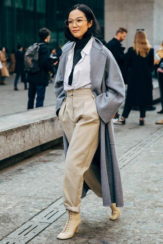 На девушке черная водолазка, белая расстегнутая рубашка, светло-коричневые свободные брюки, такого же цвета ботинки на шнуровке с толстым высоким каблуком, серое пальто оверсайз длины макси и круглые очки.