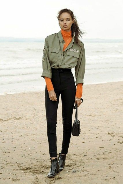 На девушке тонкая оранжевая водолазка с воротом, рубашка в маскулинном стиле цвета хаки с декоративными нашивками и карманами, черные джинсы скинни, лаковые ботинки на маленьком каблуке, черная поясная сумка и тонкая цепочка.