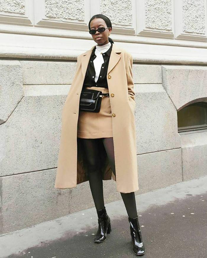На девушке белая водолазка с низким воротом, бежевая прямая юбка длины мини, тонкие полупрозрачные черные колготки, лаковые ботинки с квадратным носом и на толстом каблуке, бежевое замшевое пальто прямого кроя . Образ дополняет поясная черная сумка, тонкая цепочка и круглые черные очки.
