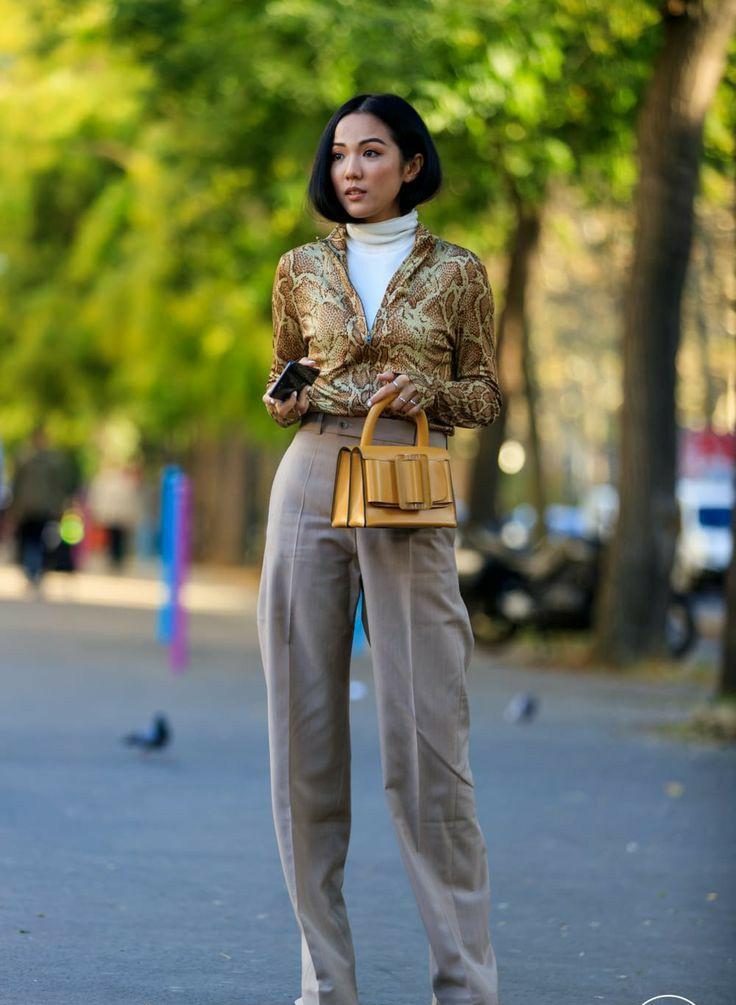 На девушке белая рубашка с длинным воротом, облегающая рубашка с анималистическим принтом и глубоким v-образным вырезом, светло-коричневые шелковые прямые брюки с со стрелой, маленькая квадратная сумка горчичного цвета.