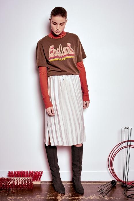 На девушке темно-оранжевая водолазка, коричневая свободная футболка с белой надписью, белая юбка плиссе длиной до середины колена, темно-серые замшевые ботфорты.