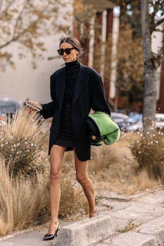 На девушке черная облегающая водолазка с воротом и пуговицами, черная юбка-карандаш длины мини, черный пиджак оверсайз прямого кроя, кожаные мюли на тонком маленьком каблуке и с заостренным носом, черные квадратные очки.