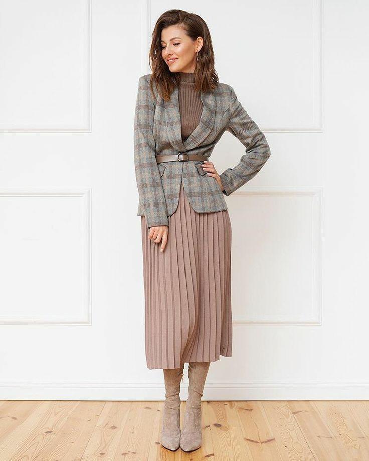 На девушке тёмно-коричневая водолазка в рубчик и с коротким воротом, бледно розовая юбка плиссе длины миди, замшевые облегающие ботфорты с заостренным носом и на каблуке, серый клетчатый пиджак прямого кроя длиной до середины бедра , подчёркнутый кожаным светло-коричневым ремнем.