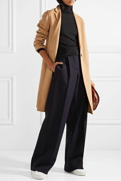 На девушке черная водолазка с воротом и подвернутыми рукавами, черные длинные брюки палаццо, белые кеды на толстой подошве, кашемировое бежевое пальто выше колена, кожаная коричневая сумка.