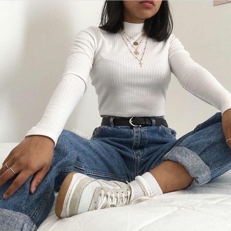 На девушке белая водолазка лапша с коротким воротом, синие джинсы бойфренды с черным кожаным ремнем,белые высокие носки, серые кроссовки, золотые тонкие цепочки.