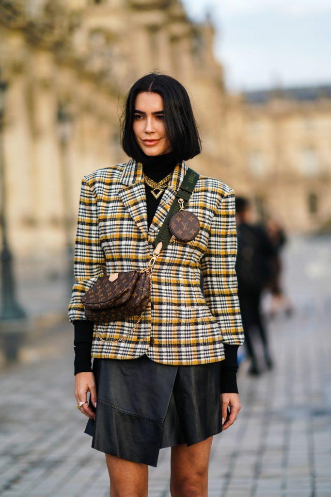 На девушке черная водолазка с длинным воротом, кожаная черная асимметричная юбка мини, желтый жакет в клетку, коричневая поясная сумка, массивная золотая цепочка.