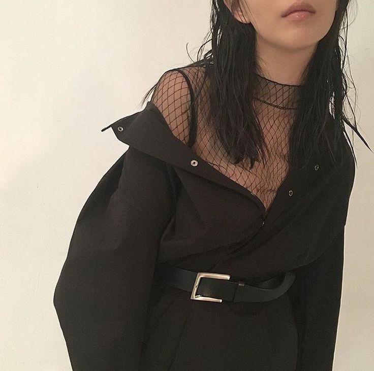 На девушке черная полупрозрачная водолазка сетка с коротким воротом, черная плотная рубашка мужского кроя, классические черные брюки с кожаными чёрным ремнём.