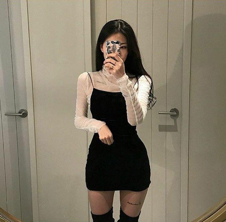 На девушке белая полупрозрачная водолазка сетка с воротом, черное облегающее платье-мини на бретельках, тонкие полупрозрачные черные колготки, замшевые облегающие ботфорты выше колена.