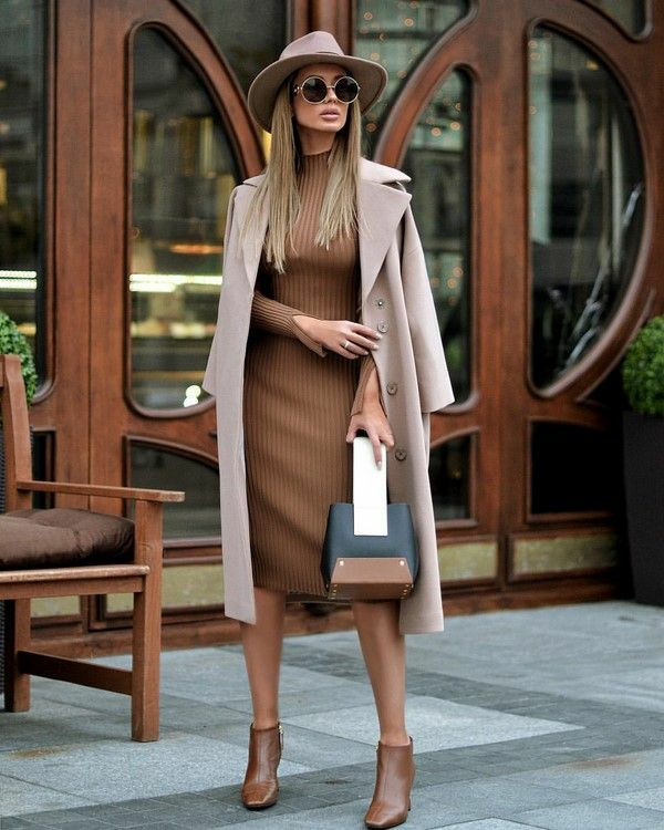 На девушке облегающее платье водолазка кофейного оттенка,длины миди, светло-розовое пальто прямого кроя длины миди, коричневые кожаные ботинки на каблуке, круглые черные очки, шляпа, сумка необычной формы.