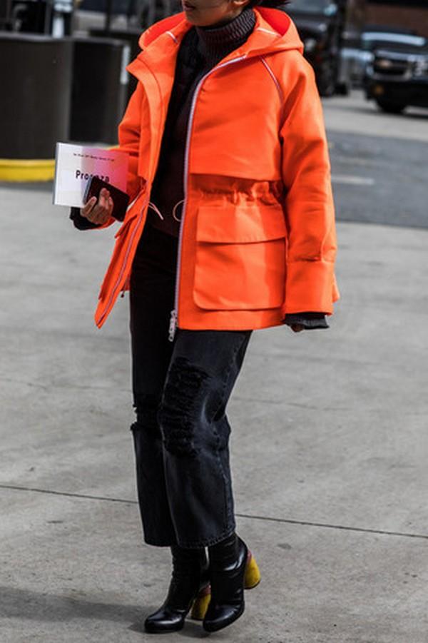 Черные брюки, обувь и свитер создают стильный лук с оранжевой паркой