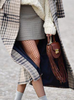 """На девушке черные чулки в сетку, прямая черно-белая юбка-мини с принтом """"гусиная лапка"""", клетчатое пальто ниже колена, объемный белый свитер крупной вязки, серые гольфы и маленькая коричневая сумка с бахромой."""
