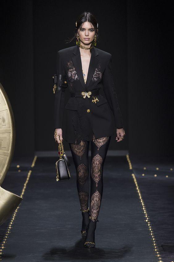 На девушке черное платье-пиджак длины мини с поясом, накладными карманами, черные босоножки на каблуке и чулки с узором. Образ дополнен золотыми аксессуарами.