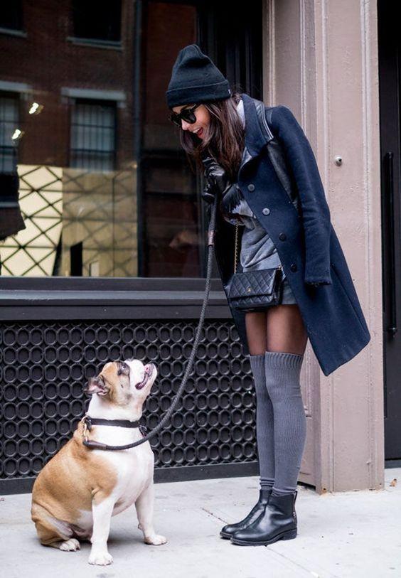 На девушке серое короткое платье, тонкие полупрозрачные черные колготки, плотные серые чулки выше колена, кожаные ботинки на маленьком широком каблуке, сине пальто, шапка и поясная сумка.