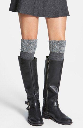 На фото серая свободная юбка-мини, кожаные высокие сапоги с ремешками и плотные серые чулки выше колена.