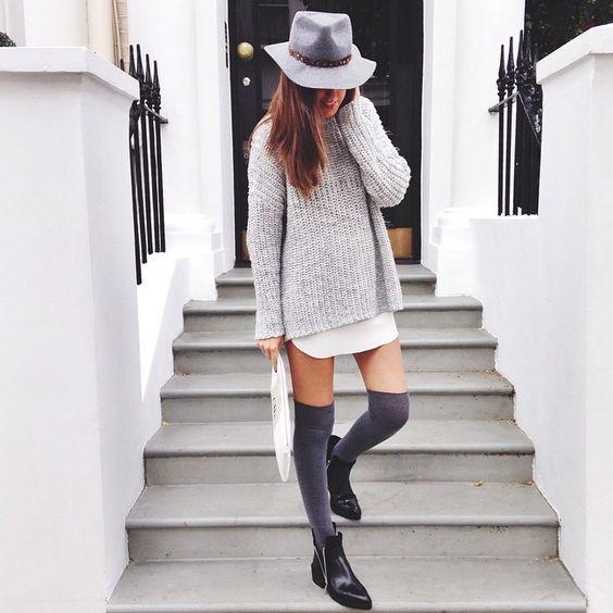 На девушке белая рубашка, сверху объемный серый свитер-платье, плотные темно-серые чулки, кожаные черные ботинки на змейке и шляпа.