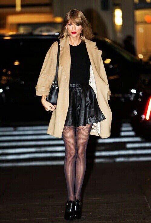 На девушке черный гольф, кожаная юбка-солнце длины мини, чулки с узором в виде прямой полоски, черные ботинки и бежевое пальто.