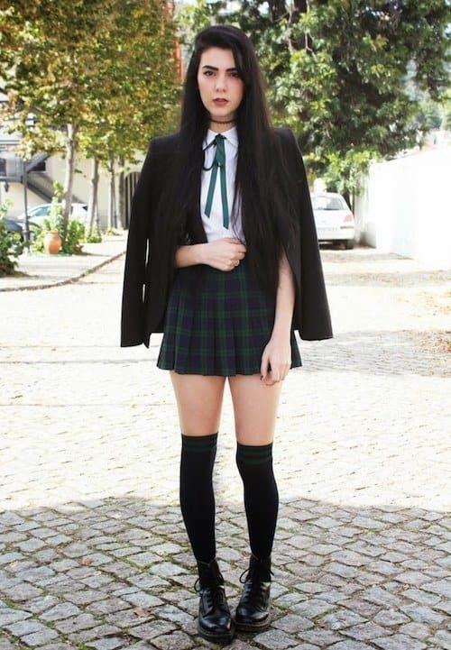 На девушке белая рубашка, черный пиджак оверсайз, короткая юбка-солнце в клетку, черные теплые чулки и ботинки на шнуровке и резиновой подошве.