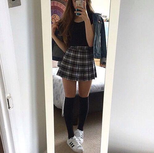 На девушке черная футболка, короткая юбка-солнце в клетку, синяя джинсовая куртка, черные теплые чулки немного выше колена, белые кроссовки.