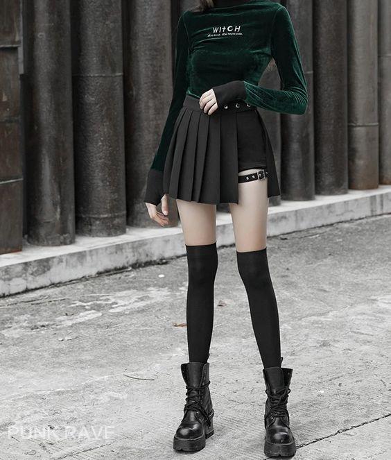 Бархатный гольф изумрудного цвета, черная мини юбка-шорты в сочетании с черными теплыми чулками выше колена и кожаными ботинками в маскулинном стиле на массивной резиновой подошве и на шнуровке.