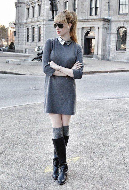На девушке прямое серое платье-мини с металлическим воротником, серые теплые чулки, кожаные свободные ботфорты и черные очки.
