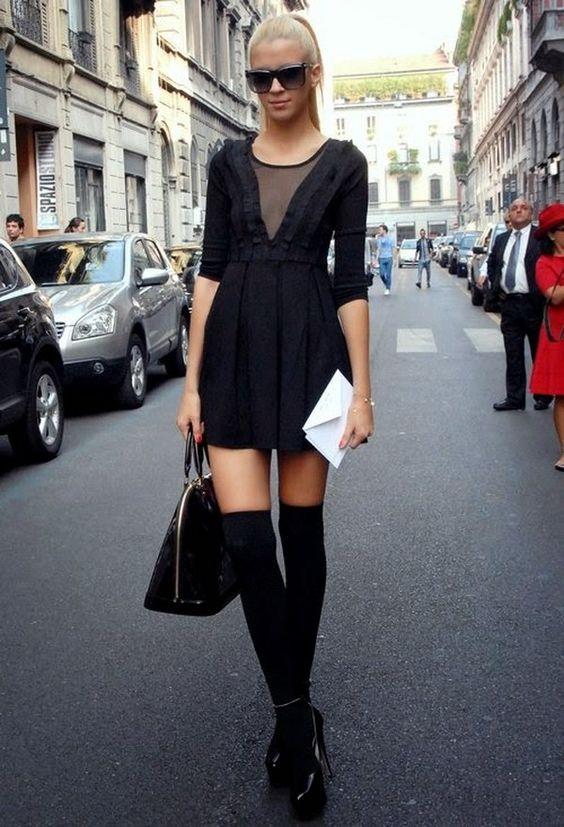 Черное платье-мини со свободной юбкой,черные теплые чулки и лаковые туфли на высоком каблуке и платформе. Образ дополняют квадратные очки и сумка.