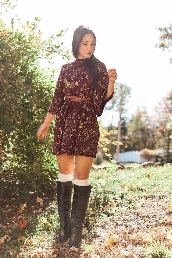 Бордовое платье-мини с узорами, талия подчеркнута коричневым тонким ремнем, белые чулки длиной до колена и свободные черные кожаные ботфорты.