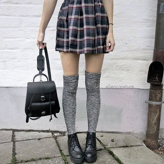 Короткая клетчатая мини юбка-солнце в сочетании с серыми плотными чулками, черными грубыми ботинками на толстой подошве и черным рюкзаком.
