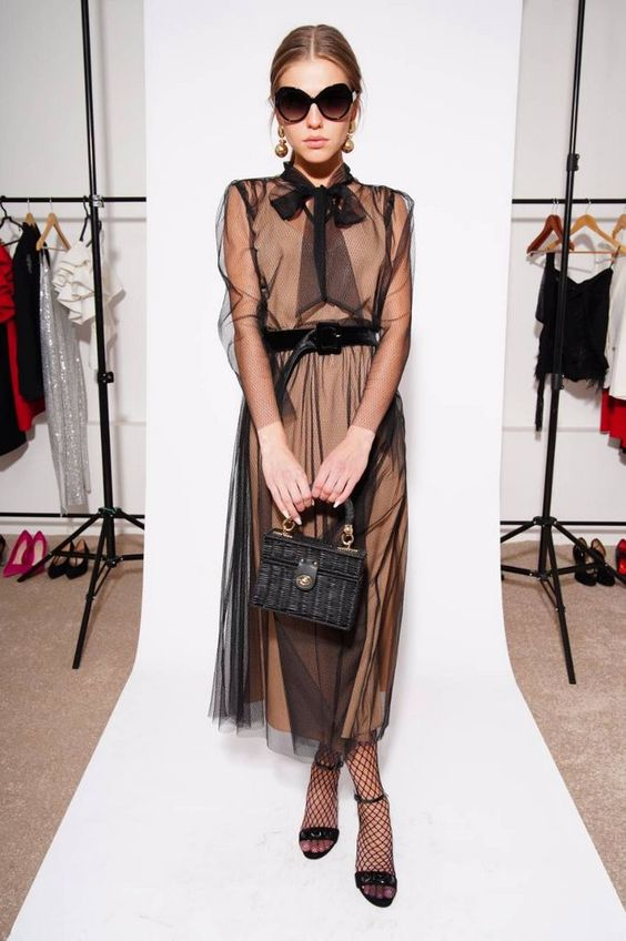 На девушке вечернее нюдовое платье-миди с черным фатином и бантом, чулки в сетку, черные босоножки на каблуке. Образ дополняет черная сумка и очки.